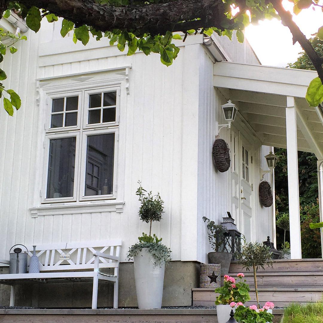 Et flott nymalt hvit hus med koselig inngangsparti
