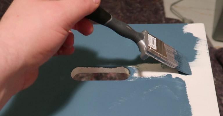 Person maler en hvit krakk blå