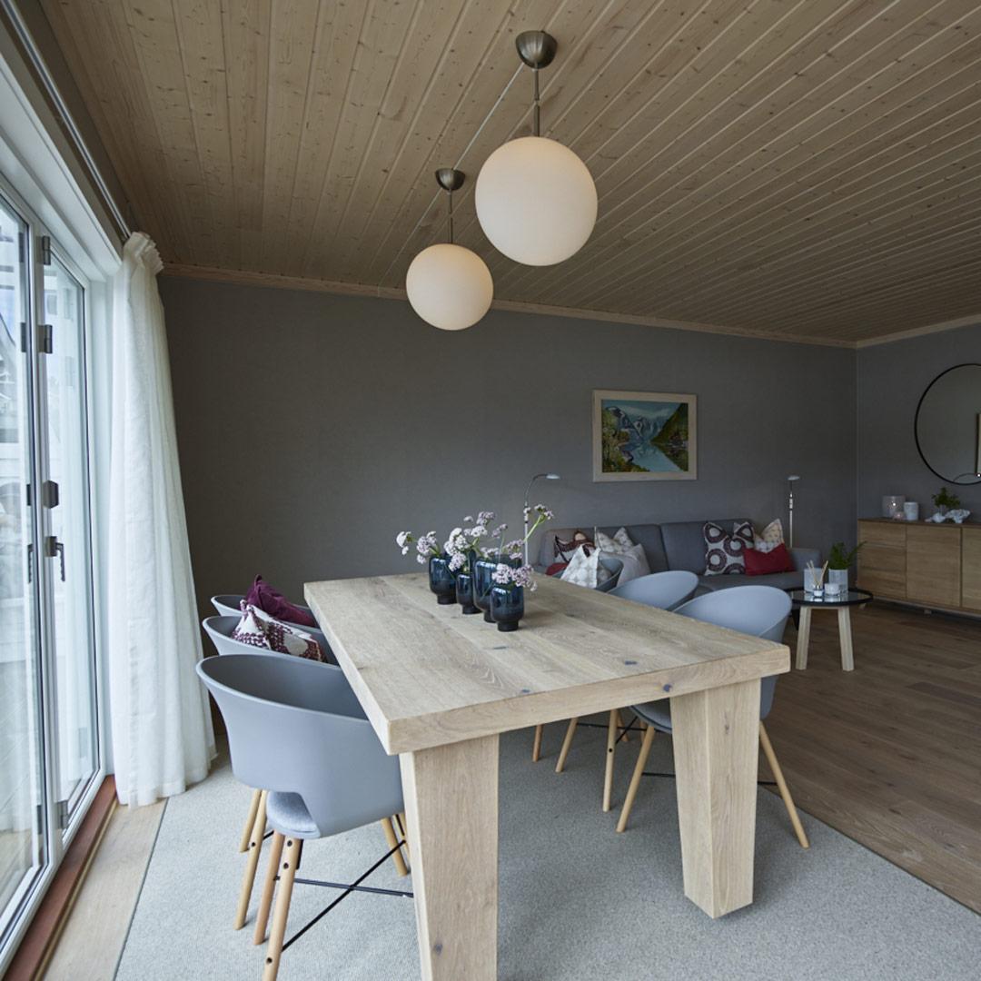 Spisebord i stuen med malt grå vegg bak