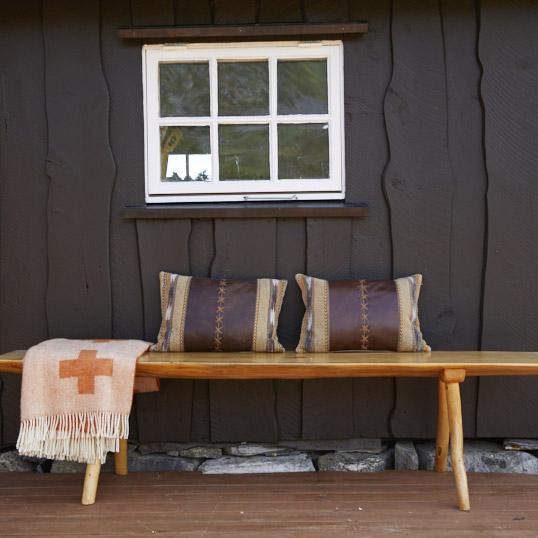 Benk med puter foran hyttevegg