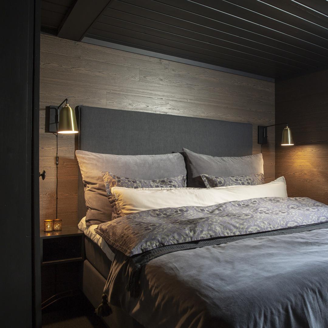 Et soverom med tak malt i mørk farge
