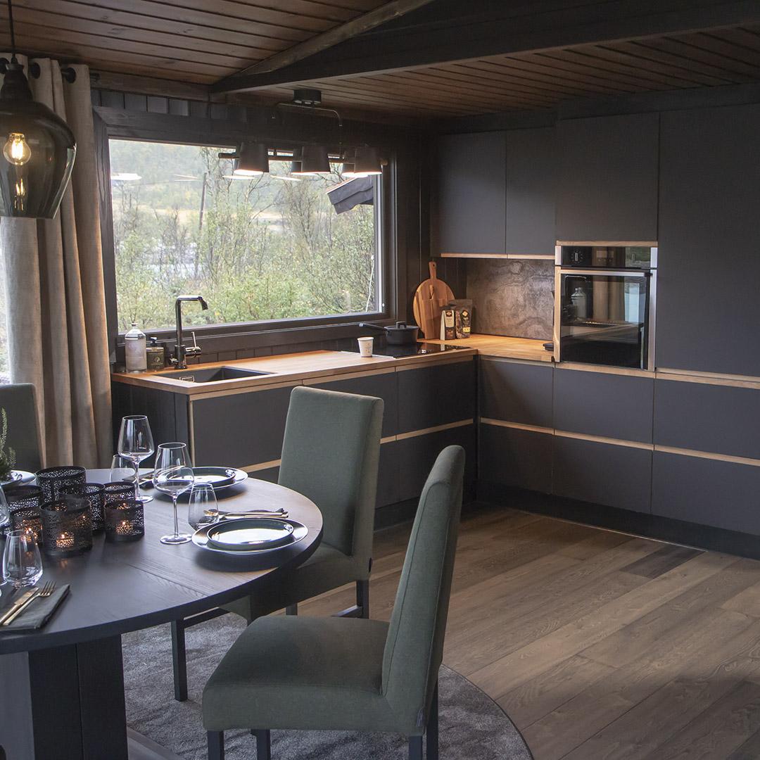 Flott kjøkken med grå skap og malt panel i taket