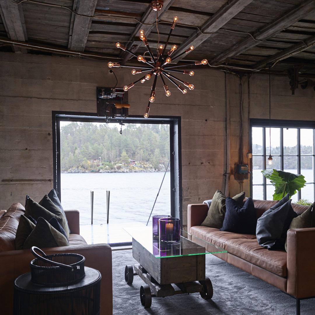 To sofaer mot hverandre foran vindu med utsikt over sjøen