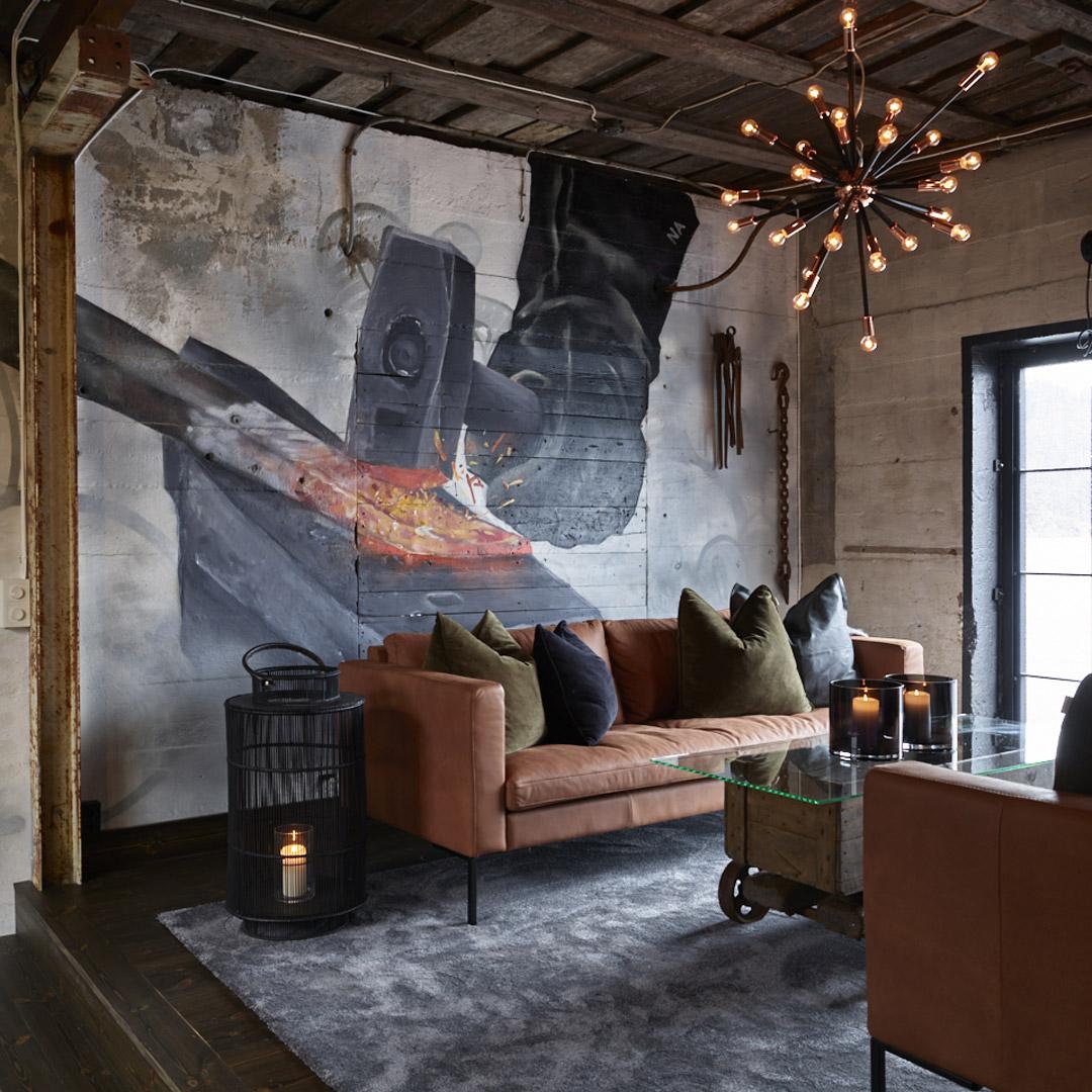 Brune sofa foran vegg med maleriet av smed