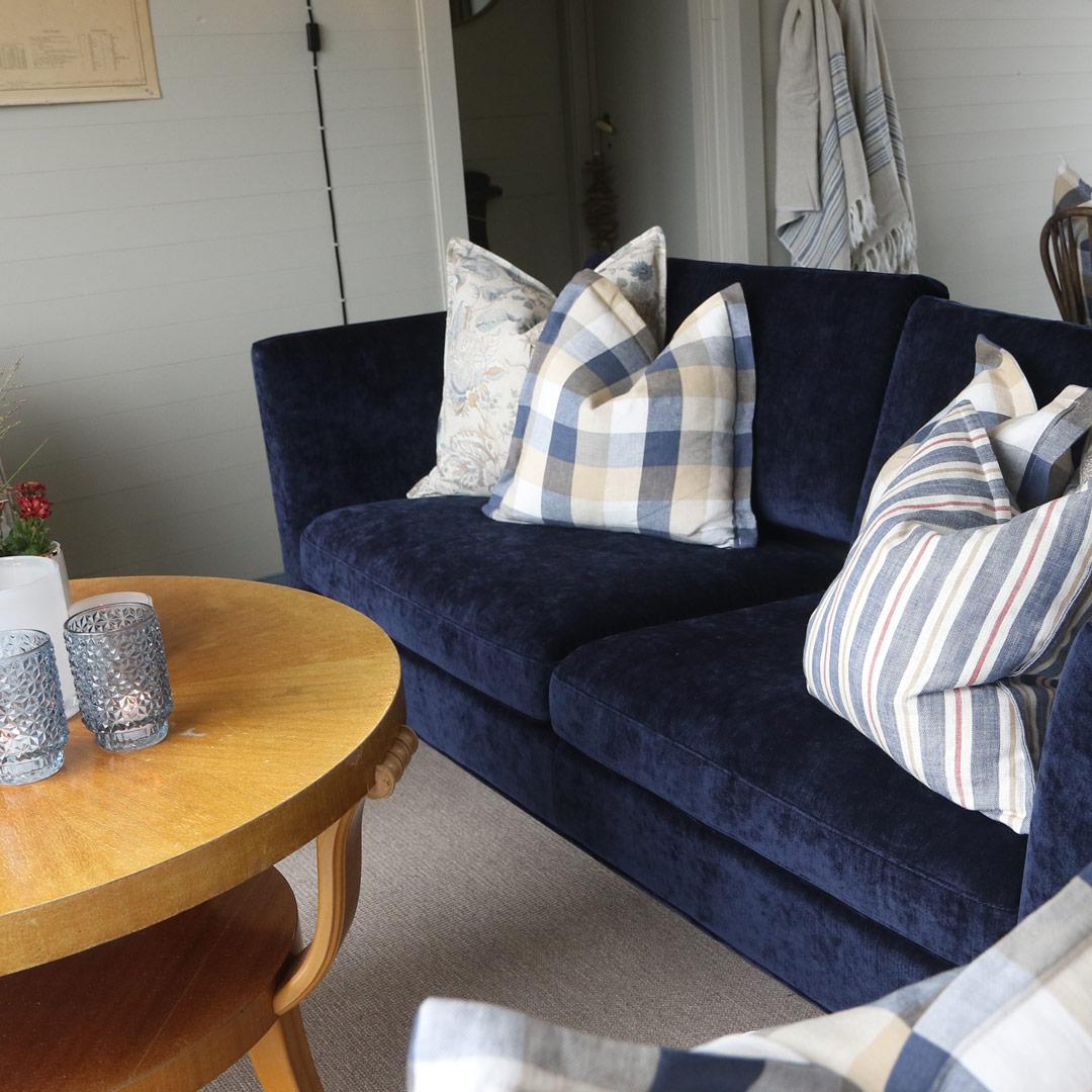 Mørekblå sofa i hytte med rutete og stripete puter