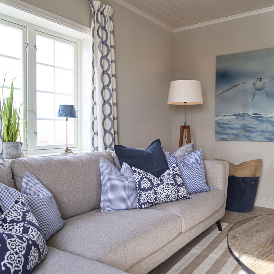 Lys stue med beige sofa og blå puter