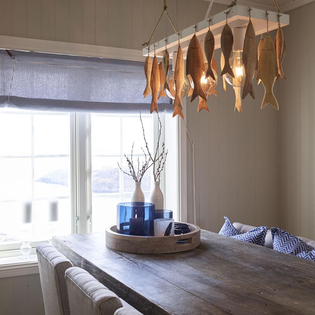Spisebord og taklampe over med utskjæringer av fisk