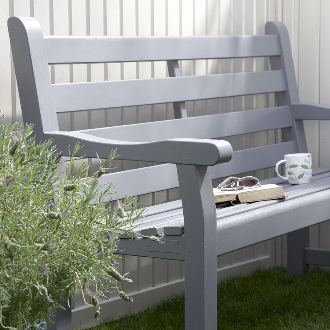grå benk med bok og kaffekopp foran hvit vegg i hagen