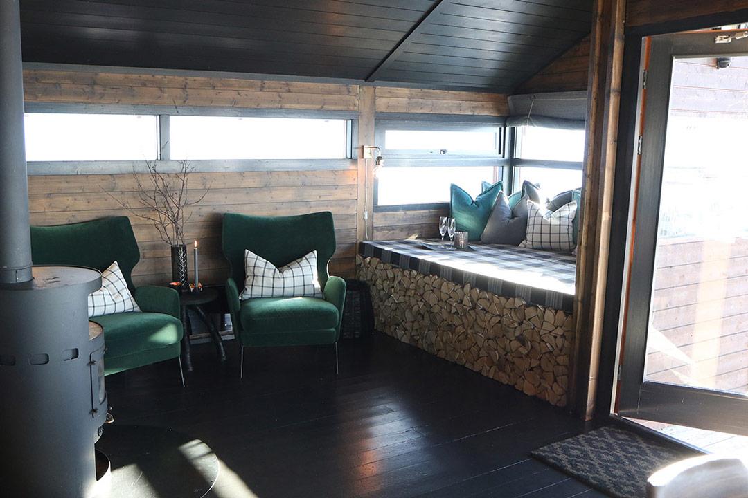 Koselig hytte med 2 grønne stoler og daybed