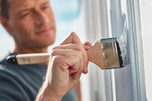 nærbilde av penselen når en mann maler et hus