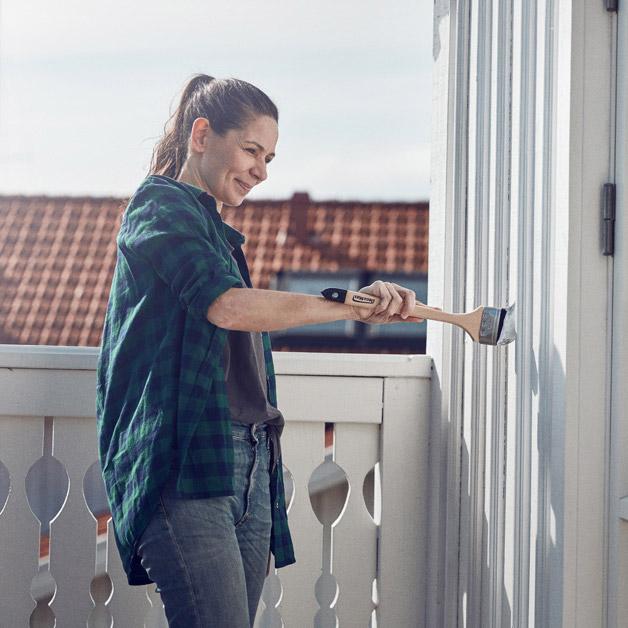 Dame som står på terrasen og maler fasaden med pensel