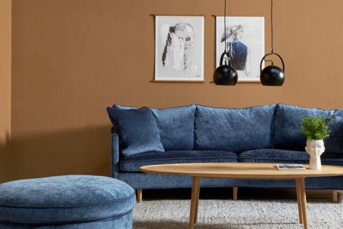 Stue i rustikk stil med blå sofa og rustikk mellomrun på veggen