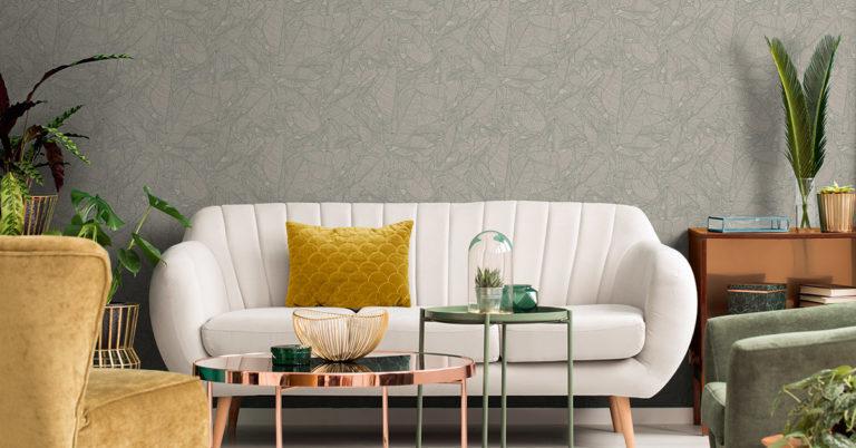 lys sofa i stue med mønstrete tapet på veggen, grønne planter på siden og bord i messing foran