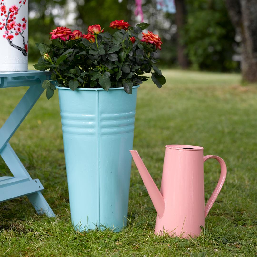 metallpotte malt i turkis stående på gresset i hagen ved siden av en vannkanne malt i rosa